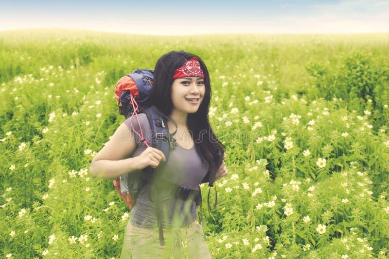 De gelukkige wandelaar bevindt zich op het bloemgebied stock foto