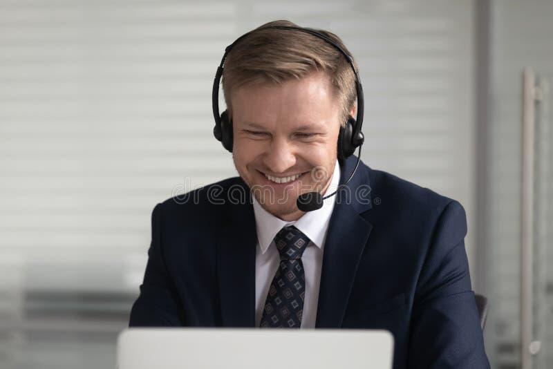 De gelukkige zakenman die kostuum draadloze hoofdtelefoon dragen maakt conferentievideogesprek stock foto's