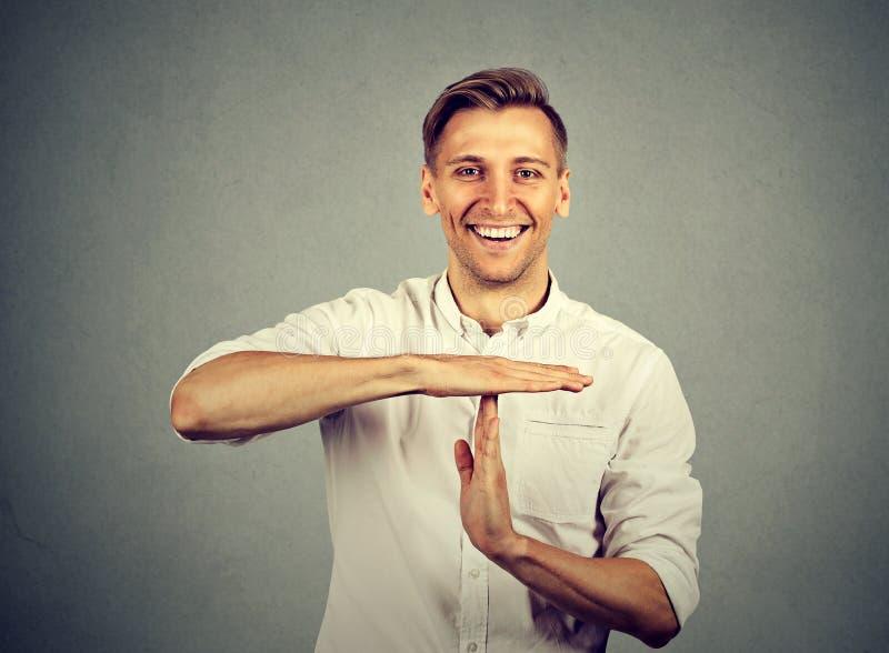 De gelukkige zakenman die tijd geven overhandigt uit gebaar stock foto