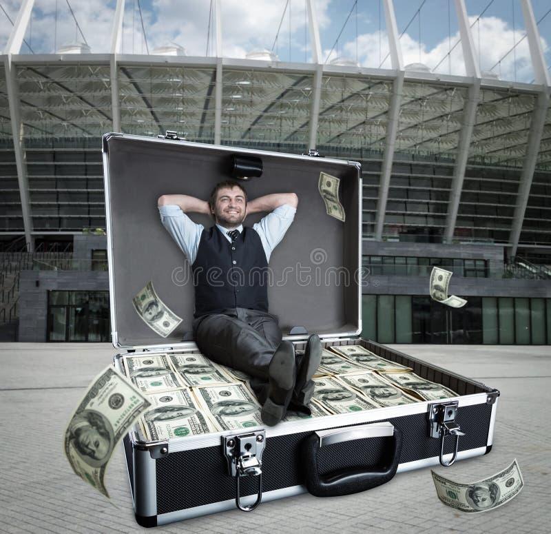 De gelukkige zakenman zit in het gevalhoogtepunt van dollars royalty-vrije stock afbeeldingen