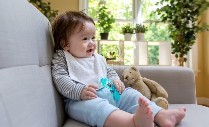 De gelukkige zitting van de babyjongen op een laag royalty-vrije stock foto