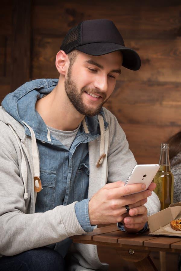 De gelukkige zitting van de hipstermens in de koffie met mobiele telefoon stock afbeelding