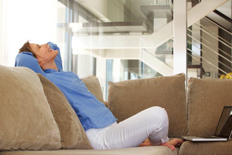 De gelukkige zitting van de middenleeftijdsvrouw op bank met laptop royalty-vrije stock fotografie