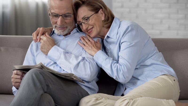 De gelukkige zitting van het gepensioneerdenpaar op laag, de krant die van de mensenlezing, dame hem koesteren stock fotografie