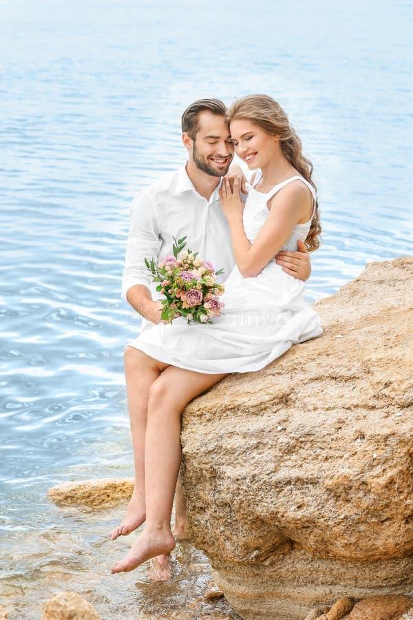 Download De Gelukkige Zitting Van Het Jonggehuwdepaar Stock Afbeelding - Afbeelding bestaande uit bruids, liefde: 107702199