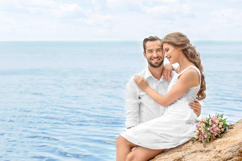 Download De Gelukkige Zitting Van Het Jonggehuwdepaar Stock Afbeelding - Afbeelding bestaande uit kaukasisch, mannetje: 107702901