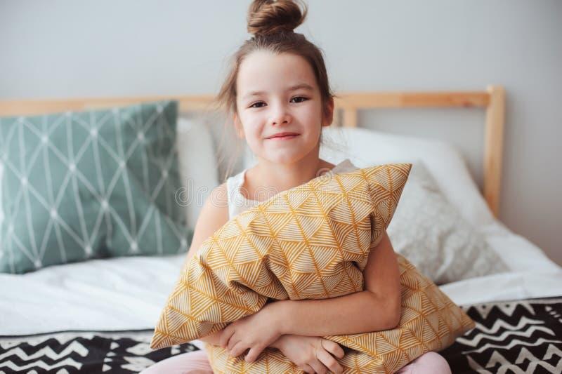de gelukkige zitting van het kindmeisje op bed en omhelzingenhoofdkussen, ontwaken in vroege ochtend of het gaan naar slaap royalty-vrije stock fotografie