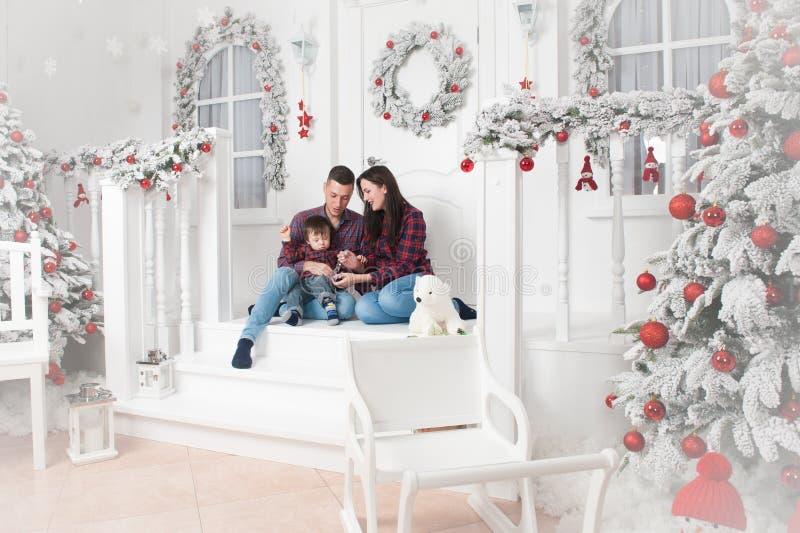 De gelukkige zitting van de de vaderbaby van de familiemoeder op portiek van Kerstmis DE stock fotografie
