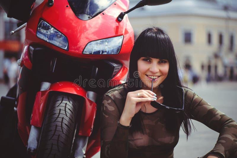 De gelukkige zitting van de vrouwenfietser dichtbij motorfiets en gelukkig, close-upbrunette met rode fiets stock foto
