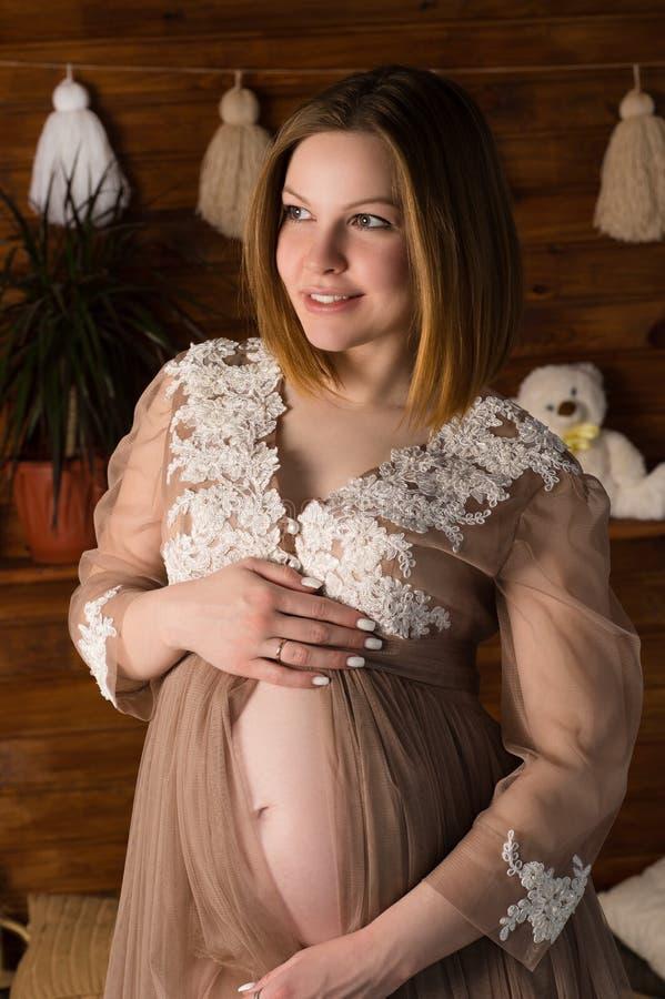 De gelukkige zwangere donkerbruine vrouw koestert buik stock afbeelding