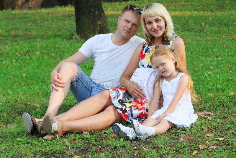 De gelukkige zwangere moeder, vader met dochter zit op gre stock fotografie