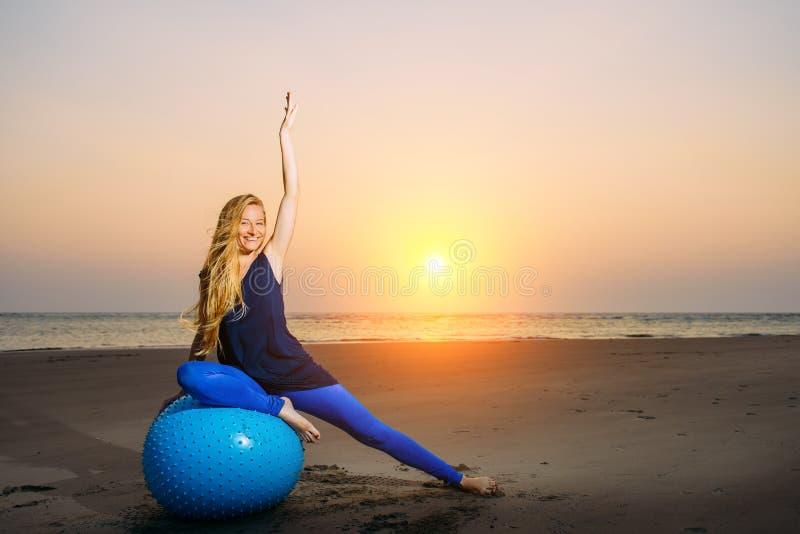 De gelukkige zwangere vrouw zit op de oefeningsbal tegen zonsondergang over het overzees Zwangerschap, sport, fitness en gezonde  stock foto's
