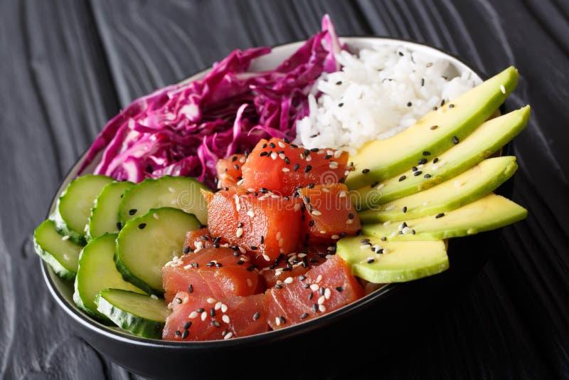 De gemarineerde kom van de tonijnpor met rijst, verse komkommers, rode kool stock foto's