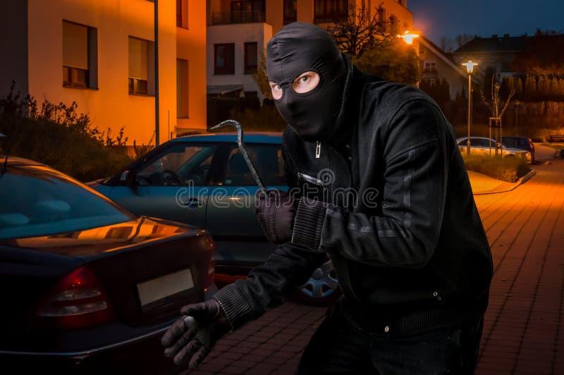 De gemaskeerde dief in balaclava met koevoet wil een auto roven royalty-vrije stock fotografie