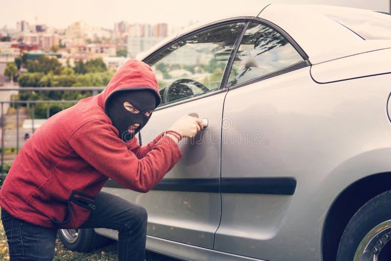 De gemaskeerde mens hurkt en breekt de auto van iemand kijkend aan de kijker De dief in hoodie en verborgen gezicht maakt poging  stock afbeeldingen