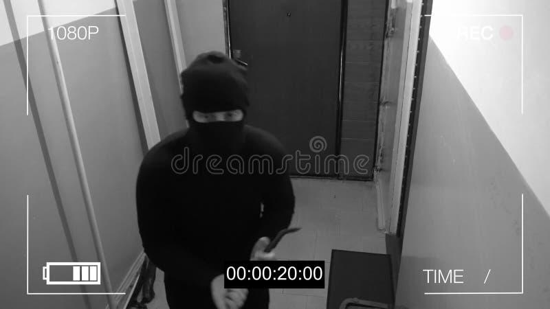 De gemaskeerde rover barstte door de deur en brak de veiligheidscamera met een bandijzer stock foto's