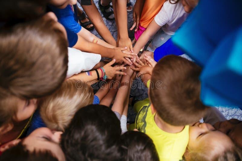 De Gemeenschap van kinderen het houden overhandigt samen close-up in de Kleuterschool stock afbeeldingen