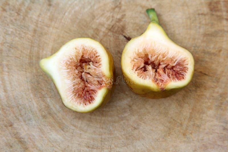 De gemeenschappelijke fig.vruchten snijden open tonend het vlees op houten achtergrond, Hoogste mening royalty-vrije stock afbeeldingen