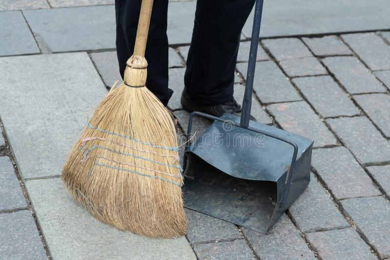 de gemeentelijke arbeider veegt de weg met bezemsteel en verzamelt huisvuil in lepel het bereikstraat van de hygiënearbeider stock afbeeldingen