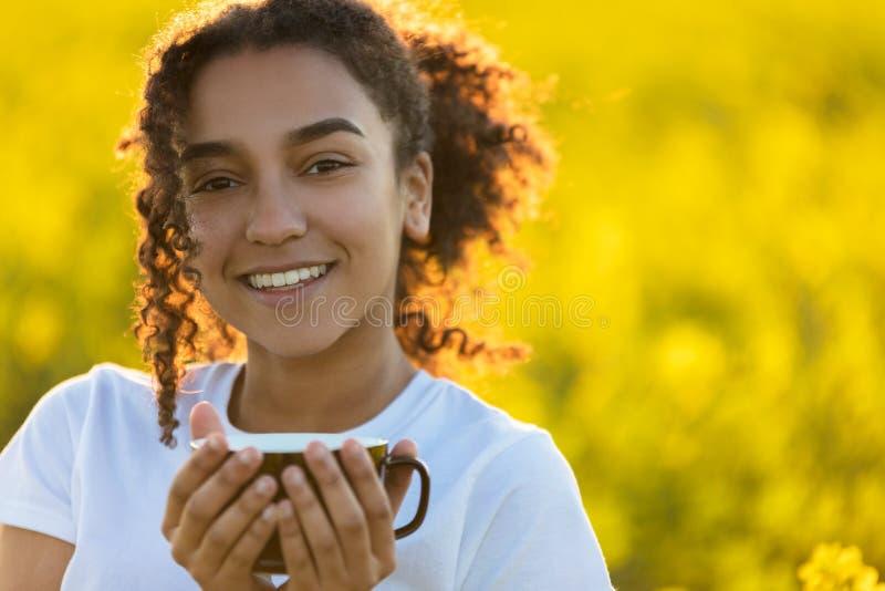 De gemengde de Vrouw van de Ras Afrikaanse Amerikaanse Tiener het Drinken Koffie overtreft stock foto