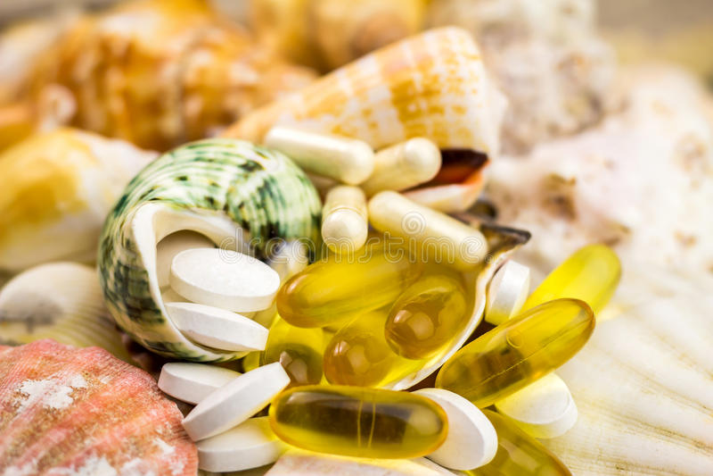 De gemengde pillen van het natuurvoedingsupplement op de mooie zeeschelpenachtergrond stock foto's