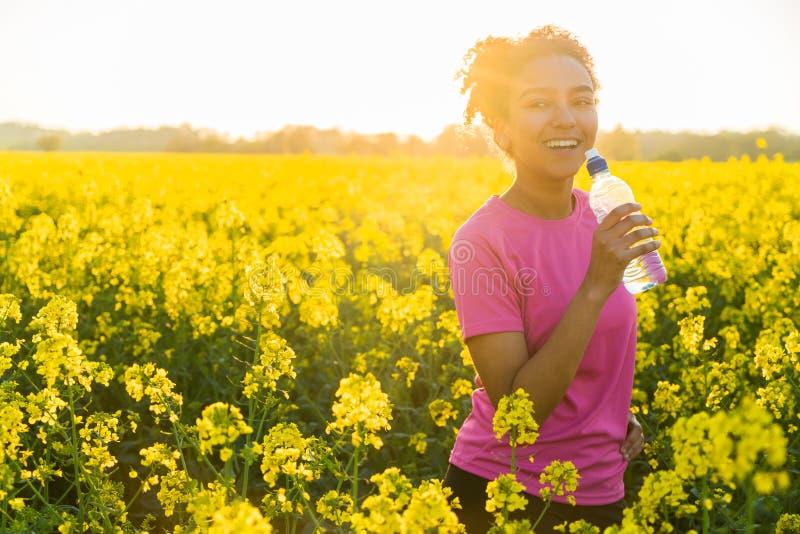 De gemengde Zonsondergang van het de Tiener Drinkwater van het Ras Afrikaanse Amerikaanse Meisje royalty-vrije stock fotografie