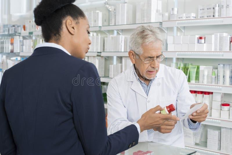 De Geneeskunde van chemicusand businesswoman with en Voorschriftdocument royalty-vrije stock afbeelding
