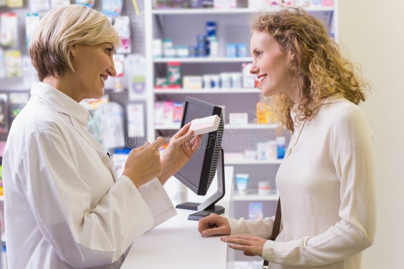 De geneeskundedoos die van de apothekerholding aan klant spreken royalty-vrije stock fotografie