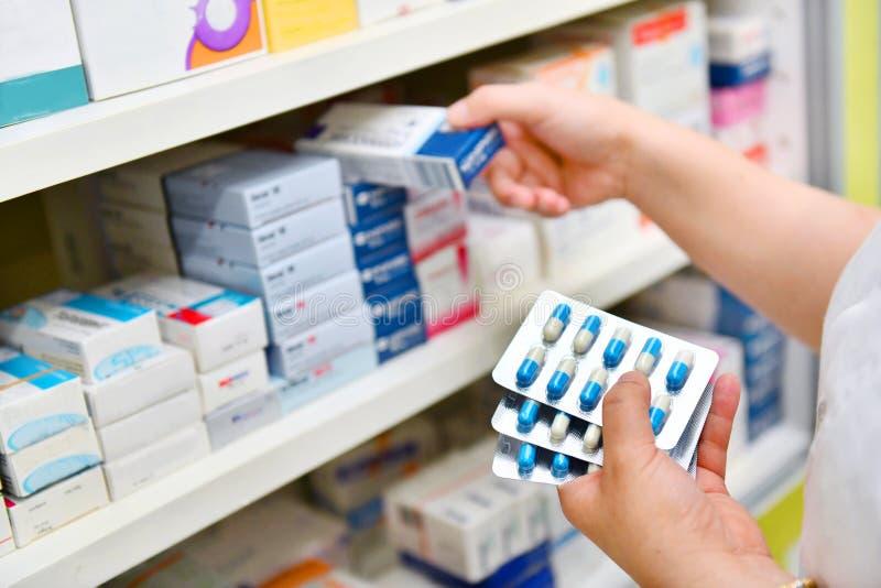 De geneeskundedoos van de apothekerholding en capsulepak royalty-vrije stock afbeelding