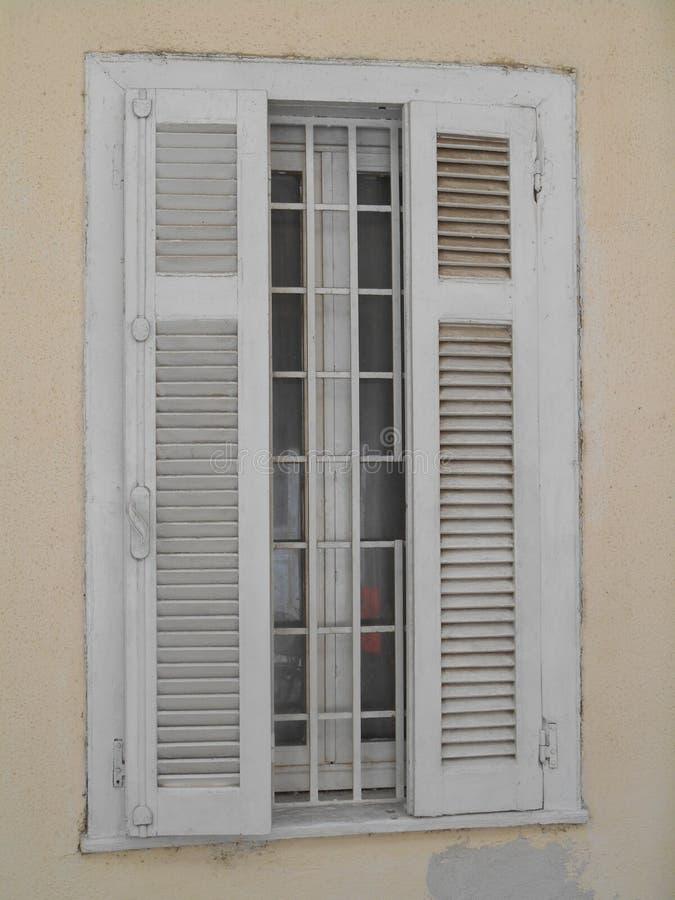 De geopende witte zonneblinden op venster met huid stemmen muren royalty-vrije stock afbeeldingen