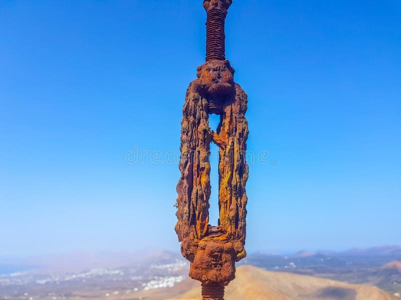 de geoxydeerde met elkaar verbonden kabels van de draadlijn in de voorgrond met hemel en overzeese bodems Beeld in Lanzarote, Spa stock foto's