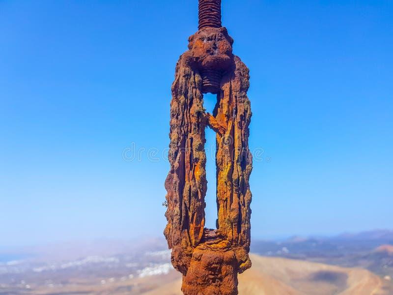 de geoxydeerde met elkaar verbonden kabels van de draadlijn in de voorgrond met hemel en overzeese bodems Beeld in Lanzarote, Spa stock fotografie