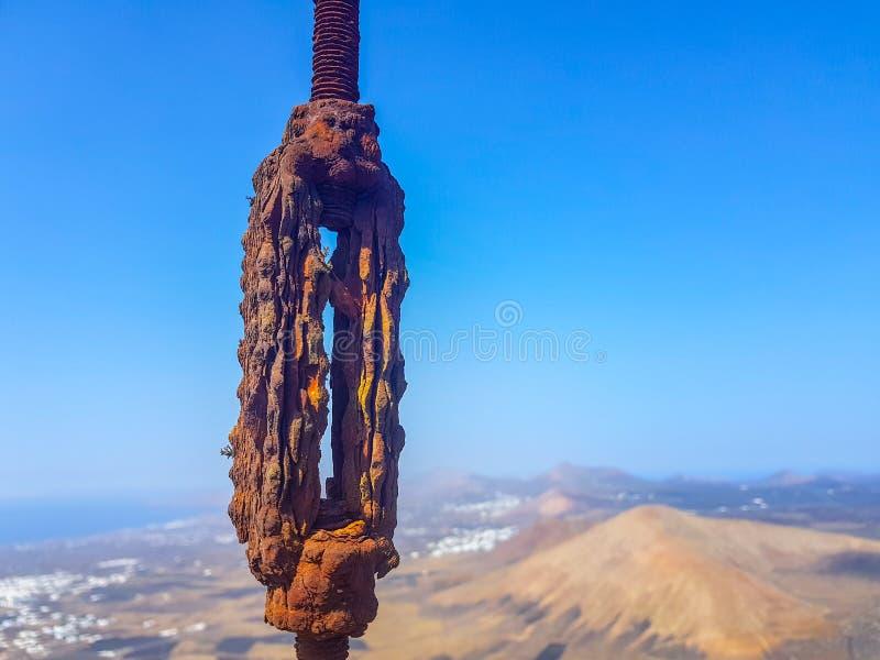 de geoxydeerde met elkaar verbonden kabels van de draadlijn in de voorgrond met hemel en overzeese bodems Beeld in Lanzarote, Spa royalty-vrije stock foto