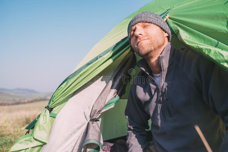 De gepaneerde mensenreiziger kijkt uit fronm tent en geniet van met zon ligh royalty-vrije stock afbeelding
