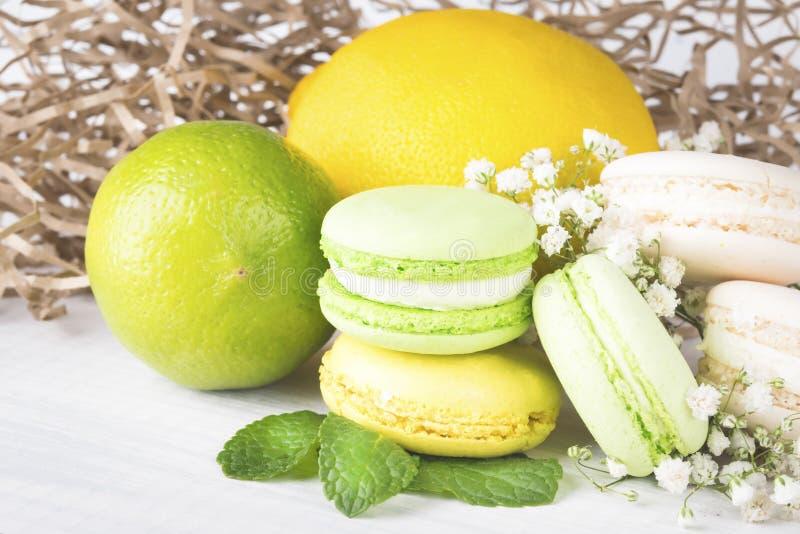 De geplaatste citrusvruchten en de koekjes liggen op een witte die lijst met kleine witte bloemen wordt verfraaid stock afbeelding