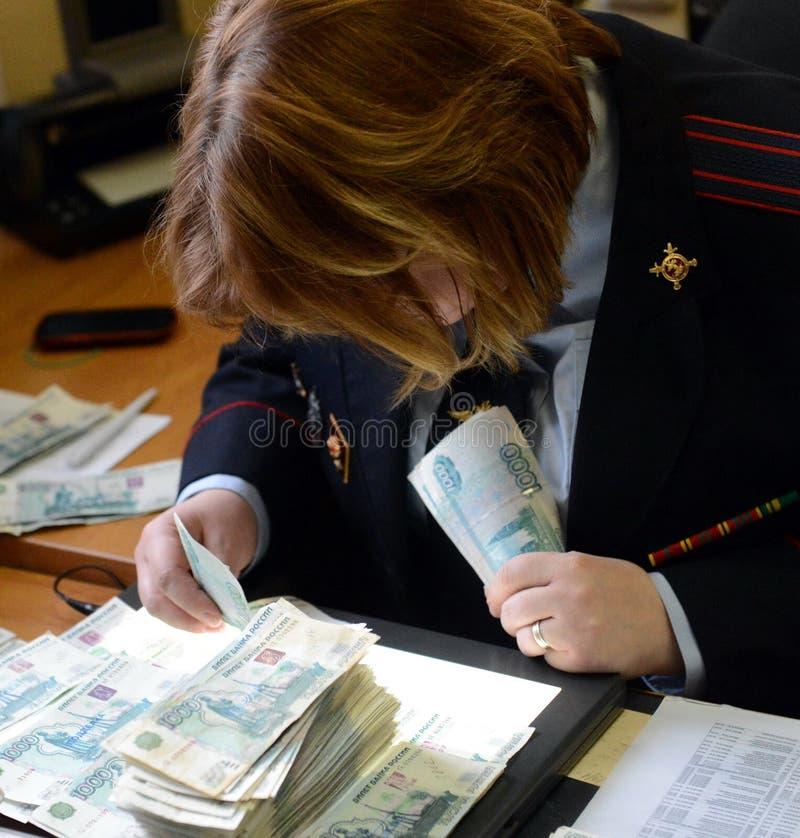 De gerechtelijke deskundige van het gerechtelijke centrum van de politie voert een studie van bankbiljetten voor authenticiteit u stock afbeelding