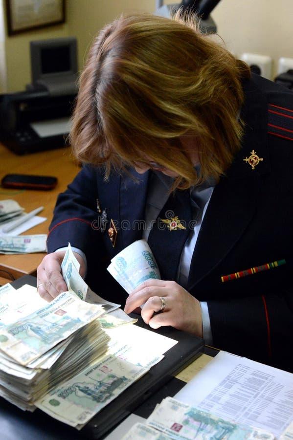 De gerechtelijke deskundige van het gerechtelijke centrum van de politie voert een studie van bankbiljetten voor authenticiteit u stock foto's