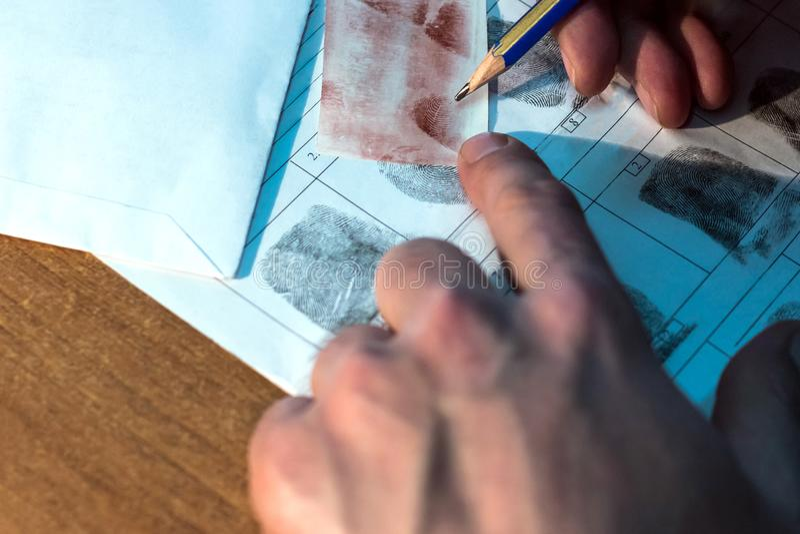 De gerechtelijke lezer vergelijkt vingerafdrukken Close-up van mannelijke handen met een potlood stock fotografie