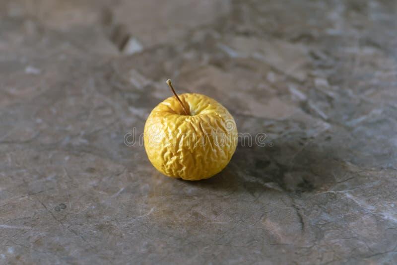 De gerimpelde gele oude appel ligt op de lijstbovenkant stock foto's