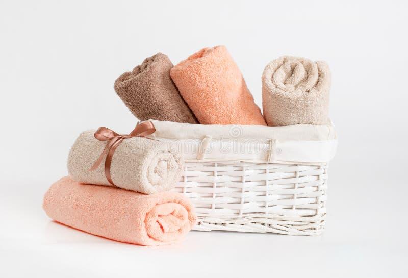De gerolde verschillende handdoeken van de kleurenbadstof met een lint tegen een witte achtergrond, handdoeken in een witte mand  stock foto