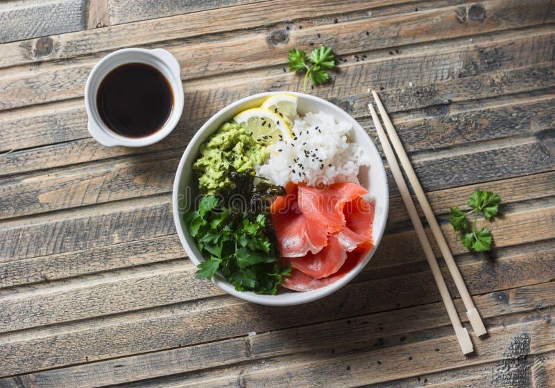 De gerookte kom van zalmsushi op houten achtergrond, hoogste mening Rijst, avocadopuree, zalm - gezond voedsel stock foto