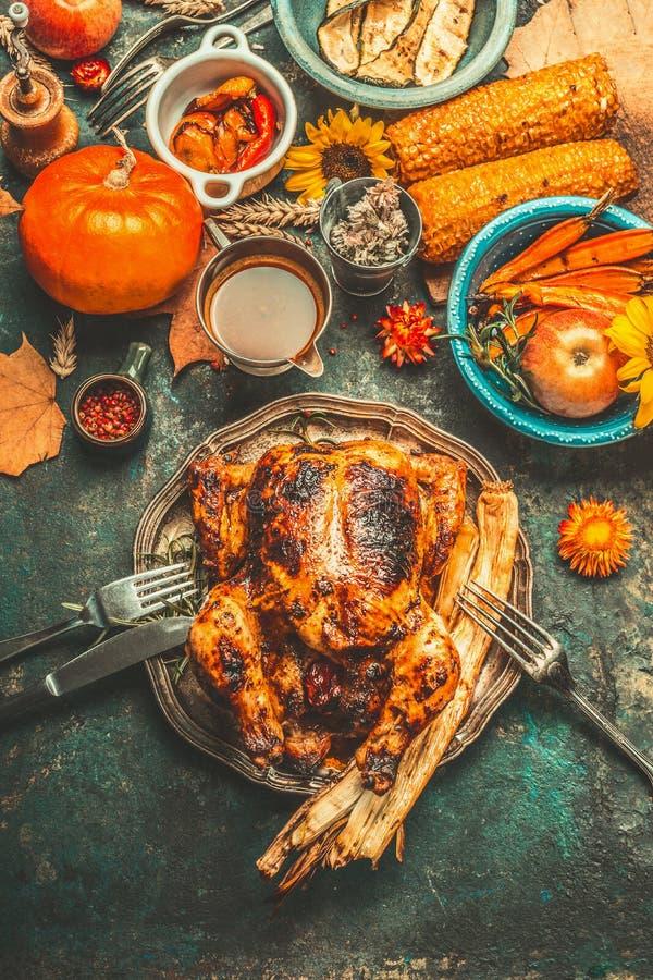 De geroosterd geheel gevuld kip of Turkije voor Thanksgiving daydiner met saus, pompoenen, graan en de herfst oogst groenten en c stock afbeelding