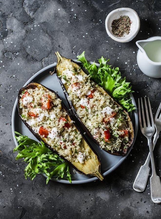 De geroosterde aubergine vulde met kouskous, tomaten, koriander met yoghurtsaus op een donkere achtergrond, hoogste mening stock fotografie