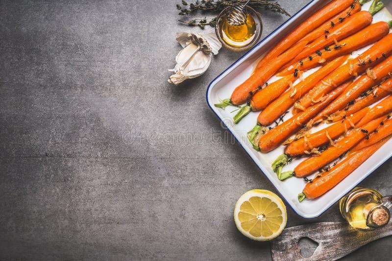 De geroosterde Baby bedekte wortelen op bakselblad met thyme, honing, knoflook en citroen op grijze concrete achtergrond, hoogste stock foto