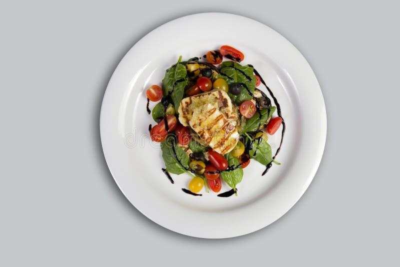 De geroosterde die Halloumi-Kaas met de saladeheks van de knoflookolijfolie wordt gegoten roosterde aubergine, kersentomaten, zwa royalty-vrije stock foto