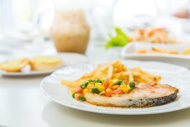 De geroosterde die maaltijd van het zalmlapje vlees met salade wordt gediend royalty-vrije stock afbeelding