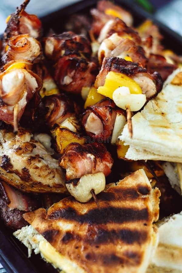 De geroosterde die vleespennen van het kippenvlees met bacon worden gerold barbecuevleespennen met groenten en geroosterd pizzabr royalty-vrije stock fotografie