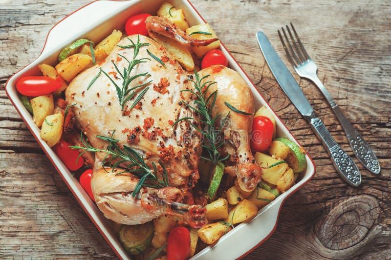 De geroosterde gehele kip vulde met groenten, de peper van de tomatenaardappel en rozemarijn op uitstekende houten lijst royalty-vrije stock fotografie