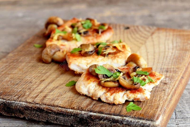 De geroosterde gesneden borst van Turkije met kaas, paddestoelen en peterselie op een knipselraad en een oude houten lijst royalty-vrije stock foto