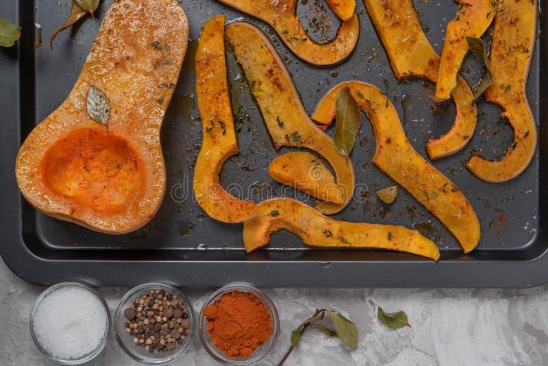 De geroosterde gesneden butternut pompoen kruidde met zoute, paprika, peper en thyme op gebakken schotel royalty-vrije stock foto's